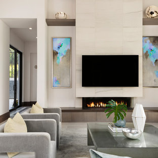 Inredning av ett modernt stort allrum med öppen planlösning, med vita väggar, klinkergolv i porslin, en väggmonterad TV, beiget golv, en bred öppen spis och en spiselkrans i trä