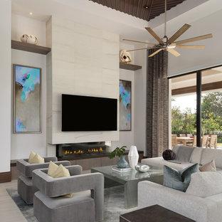 Foto på ett stort funkis allrum med öppen planlösning, med vita väggar, en bred öppen spis, en väggmonterad TV, klinkergolv i porslin, en spiselkrans i trä och beiget golv