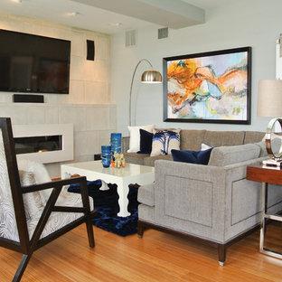 Diseño de salón tipo loft, actual, de tamaño medio, con paredes grises, suelo de bambú, chimenea tradicional, marco de chimenea de hormigón, televisor colgado en la pared y suelo naranja