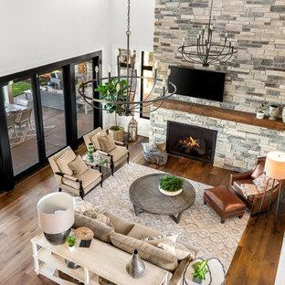 Пример оригинального дизайна: огромная открытая гостиная комната в стиле кантри с белыми стенами, паркетным полом среднего тона, стандартным камином, фасадом камина из камня и телевизором на стене