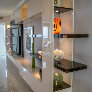 Modelo de salón abierto, moderno, grande, sin chimenea, con paredes blancas, suelo de mármol, pared multimedia y suelo beige