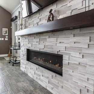 他の地域の大きいトランジショナルスタイルのおしゃれなリビング (グレーの壁、磁器タイルの床、石材の暖炉まわり、壁掛け型テレビ、グレーの床、横長型暖炉) の写真