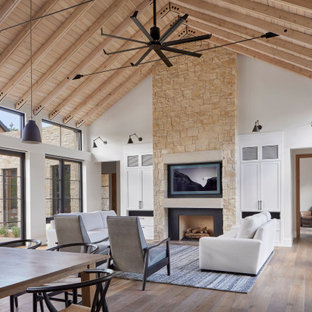 Living room - large cottage open concept medium tone wood floor, brown floor and vaulted ceiling living room idea in Denver with white walls, a standard fireplace, a metal fireplace and a wall-mounted tv
