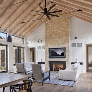 Lantlig inredning av ett stort allrum med öppen planlösning, med vita väggar, mellanmörkt trägolv, en standard öppen spis, en spiselkrans i metall, en väggmonterad TV och brunt golv