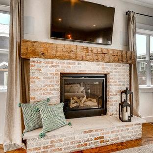 Imagen de salón abierto, campestre, de tamaño medio, con paredes grises, suelo de madera en tonos medios, chimenea tradicional, marco de chimenea de ladrillo, televisor colgado en la pared y suelo marrón