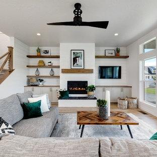 Großes, Offenes Landhaus Wohnzimmer mit weißer Wandfarbe, hellem Holzboden, Kamin, Kaminumrandung aus Backstein, Wand-TV und beigem Boden in Boise