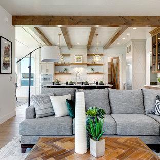 Ispirazione per un grande soggiorno country aperto con pareti bianche, parquet chiaro, camino classico, cornice del camino in mattoni, TV a parete e pavimento beige