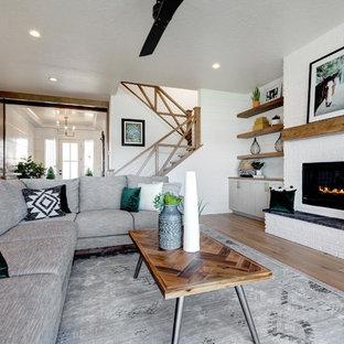 Lantlig inredning av ett stort allrum med öppen planlösning, med vita väggar, ljust trägolv, en standard öppen spis, en spiselkrans i tegelsten, en väggmonterad TV och beiget golv