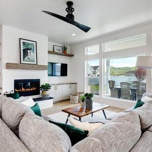 Modelo de salón abierto, campestre, grande, con paredes blancas, suelo de madera clara, chimenea tradicional, marco de chimenea de ladrillo, televisor colgado en la pared y suelo beige