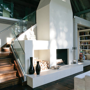 Idee per un soggiorno country di medie dimensioni con libreria, parquet scuro, pareti grigie, nessuna TV e camino bifacciale