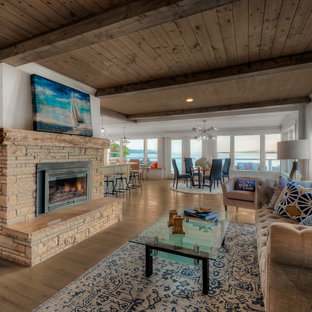 Photo of a beach style open concept living room in Seattle with white walls, medium hardwood floors, a standard fireplace, brown floor and wood.