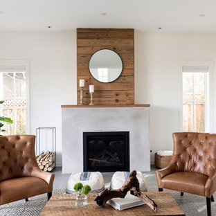 Mid-sized farmhouse open concept concrete floor and gray floor living room photo in San Francisco with white walls and a wood fireplace surround