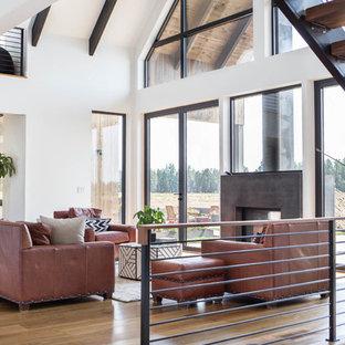 Ispirazione per un grande soggiorno moderno aperto con pareti bianche, pavimento in legno massello medio, camino bifacciale, cornice del camino in cemento e nessuna TV