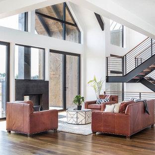 Immagine di un grande soggiorno design aperto con pavimento in legno massello medio, pareti bianche, camino bifacciale, cornice del camino in cemento, nessuna TV e pavimento marrone
