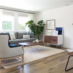 Ejemplo de salón para visitas abierto, de estilo de casa de campo, grande, con paredes blancas, suelo de madera en tonos medios, chimenea de esquina, marco de chimenea de piedra y televisor colgado en la pared
