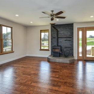 Esempio di un grande soggiorno country aperto con sala formale, pareti beige, pavimento in legno massello medio, stufa a legna, cornice del camino in pietra, nessuna TV e pavimento marrone