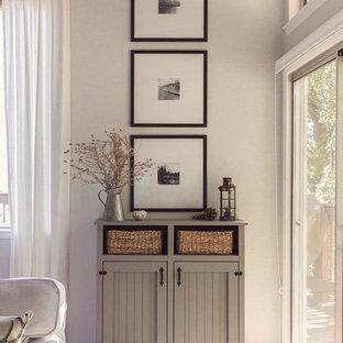 Ispirazione per un grande soggiorno country aperto con pareti grigie, parquet chiaro, camino classico, cornice del camino in pietra e pavimento grigio
