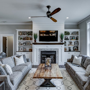 This is an example of an arts and crafts living room in Other with grey walls, dark hardwood floors and a wall-mounted tv.