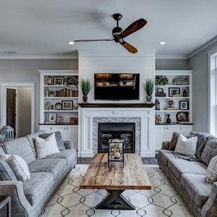 Aménagement d'un salon craftsman avec un mur gris, un sol en bois foncé et un téléviseur fixé au mur.