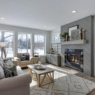Modelo de salón abierto, de estilo de casa de campo, de tamaño medio, sin televisor, con paredes blancas, suelo laminado, chimenea tradicional, marco de chimenea de baldosas y/o azulejos y suelo gris