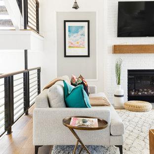 Diseño de salón abierto, tradicional renovado, con paredes blancas, suelo de madera clara, chimenea tradicional, marco de chimenea de ladrillo, televisor colgado en la pared y suelo marrón