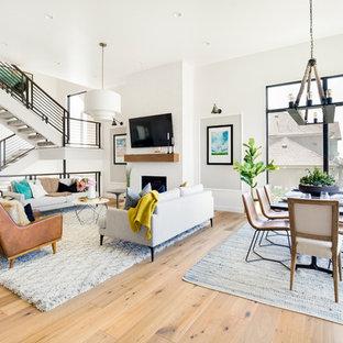 Foto de salón abierto, tradicional renovado, con paredes blancas, suelo de madera clara, chimenea tradicional, marco de chimenea de ladrillo, televisor colgado en la pared y suelo marrón