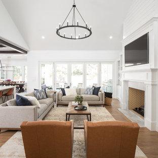 Bild på ett lantligt allrum med öppen planlösning, med vita väggar, mellanmörkt trägolv, en standard öppen spis, en spiselkrans i sten, en väggmonterad TV och brunt golv
