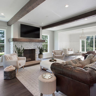 Example of a large country open concept dark wood floor and brown floor living room design in Kansas City with gray walls, a wood stove, a stone fireplace and a wall-mounted tv