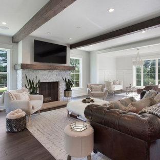 Esempio di un grande soggiorno country aperto con pareti grigie, parquet scuro, stufa a legna, cornice del camino in pietra, TV a parete e pavimento marrone