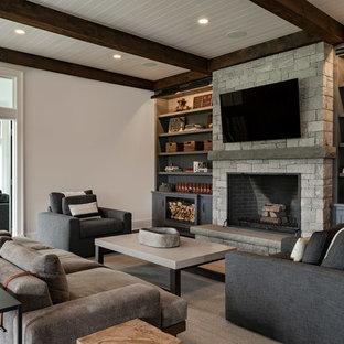 Ejemplo de salón cerrado, campestre, grande, con paredes blancas, chimenea tradicional, marco de chimenea de piedra, televisor colgado en la pared, suelo de madera oscura y suelo negro