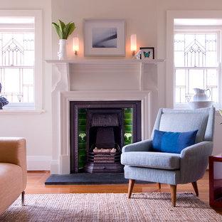 Réalisation d'un salon victorien avec un sol en bois brun, une cheminée standard, un mur blanc et un manteau de cheminée en carrelage.