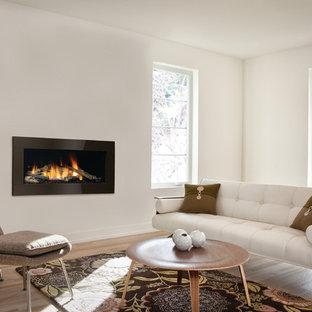 Immagine di un soggiorno contemporaneo di medie dimensioni e aperto con pareti bianche, parquet chiaro, camino sospeso, cornice del camino in intonaco, nessuna TV e pavimento beige