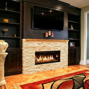 Ejemplo de salón para visitas abierto, actual, grande, con paredes verdes, suelo de madera en tonos medios, chimenea lineal, marco de chimenea de piedra, televisor colgado en la pared y suelo marrón