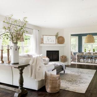 Diseño de salón abierto, moderno, grande, con paredes beige, suelo de madera oscura, chimenea de esquina, marco de chimenea de ladrillo y suelo marrón