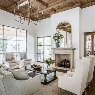Modelo de salón abierto, clásico renovado, con paredes blancas, suelo de madera oscura y chimenea tradicional