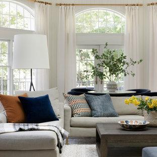 ミネアポリスの大きいトランジショナルスタイルのおしゃれなリビング (白い壁、無垢フローリング、壁掛け型テレビ、茶色い床) の写真