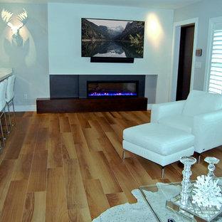 Diseño de salón abierto, minimalista, pequeño, con paredes grises, suelo de baldosas de porcelana, chimenea tradicional, marco de chimenea de madera, televisor colgado en la pared y suelo marrón