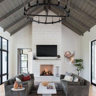 Ejemplo de salón de estilo de casa de campo con paredes blancas, suelo de madera en tonos medios, chimenea tradicional, marco de chimenea de piedra, televisor colgado en la pared y suelo marrón