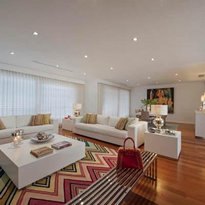 Inspiration for a contemporary open concept medium tone wood floor living room remodel in Other with white walls