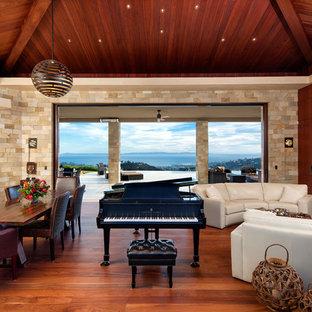 Esempio di un ampio soggiorno tropicale aperto con pareti beige, parquet scuro, camino bifacciale, cornice del camino in pietra e nessuna TV