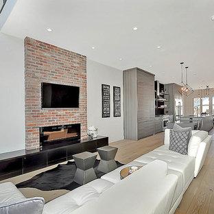 Bild på ett industriellt allrum med öppen planlösning, med grå väggar, ljust trägolv, en hängande öppen spis, en spiselkrans i tegelsten och en väggmonterad TV