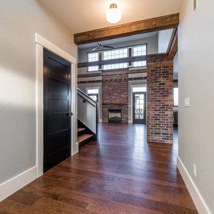 Bild på ett stort industriellt allrum med öppen planlösning, med en standard öppen spis, en spiselkrans i tegelsten, ett finrum, grå väggar och mellanmörkt trägolv