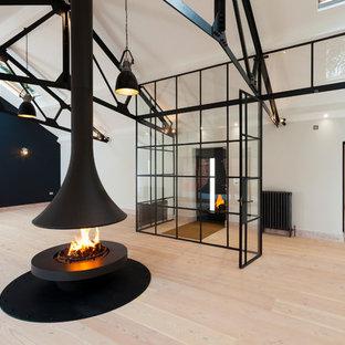 ケントの巨大なモダンスタイルのおしゃれなLDK (フォーマル、白い壁、淡色無垢フローリング、吊り下げ式暖炉、金属の暖炉まわり、テレビなし) の写真