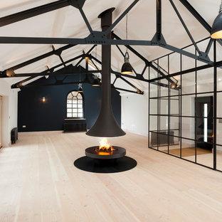 ケントの巨大なインダストリアルスタイルのおしゃれなLDK (フォーマル、黒い壁、淡色無垢フローリング、吊り下げ式暖炉、金属の暖炉まわり、壁掛け型テレビ) の写真