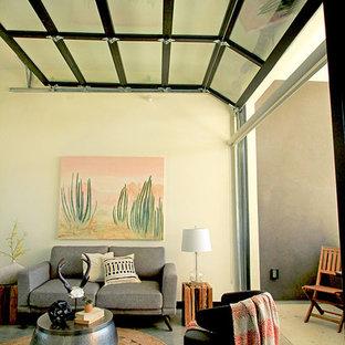 Ispirazione per un soggiorno moderno di medie dimensioni e chiuso con libreria, pareti beige, pavimento in cemento, nessun camino, nessuna TV e pavimento grigio