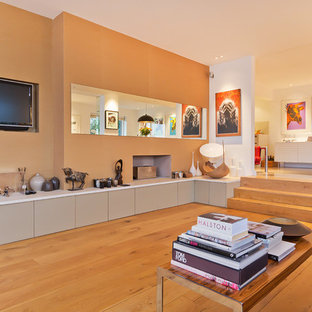 This is an example of a contemporary open plan living room in Sussex with beige walls, medium hardwood flooring and a wall mounted tv.