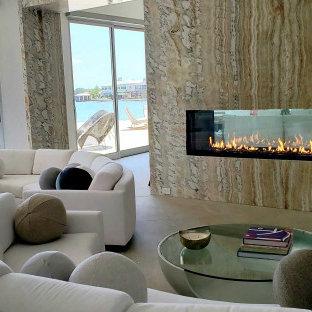 Esempio di un ampio soggiorno design aperto con sala formale, pareti marroni, pavimento in ardesia, camino bifacciale e nessuna TV