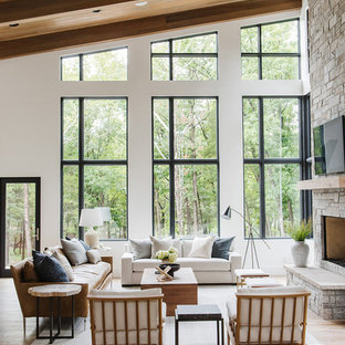 Inspiration for a large country open concept light wood floor living room remodel in Salt Lake City with white walls, a standard fireplace, a stone fireplace and a concealed tv