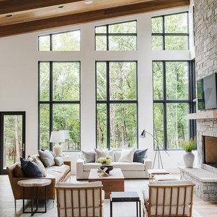 Ejemplo de salón abierto, de estilo de casa de campo, grande, con paredes blancas, suelo de madera clara, chimenea tradicional, marco de chimenea de piedra y televisor retractable