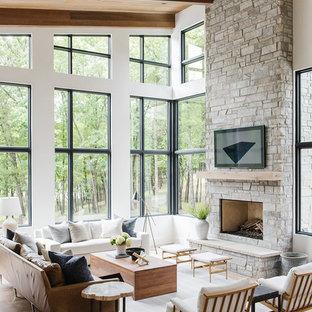 ソルトレイクシティの大きいカントリー風おしゃれなLDK (白い壁、淡色無垢フローリング、標準型暖炉、石材の暖炉まわり、壁掛け型テレビ、ベージュの床) の写真